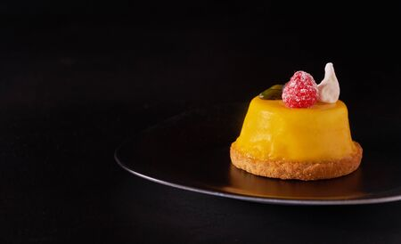 Mango mousse cake dessert covered with yellow glaze on black plate Imagens