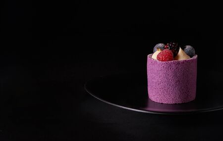 Purple berry mousse cake with blackberry, blueberry and raspberry on black plate Imagens