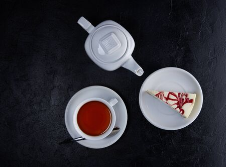 Pieces of cheesecake, cup of tea and teapot on black background. Top view, Flat lay