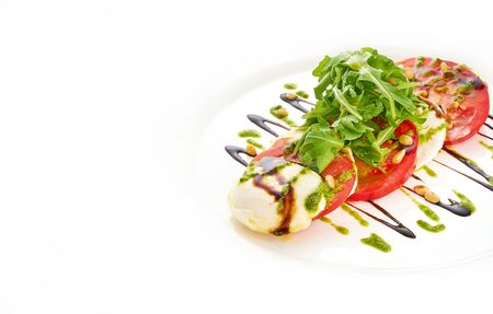 Salad with mozarella cheese, tomatoes, arugula and pesto sauce in white plate. Imagens