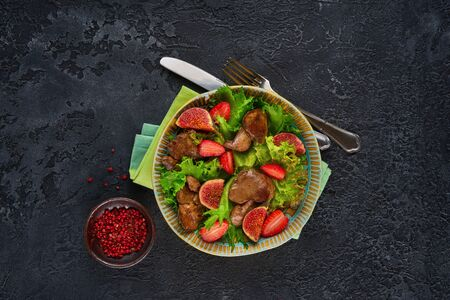 Green salad with liver and strawberry on dark rustic background