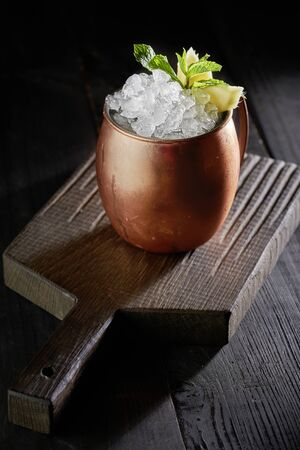 Cold Moscow Mule cocktail in copper mug on the rustic wooden background