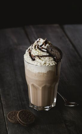 Delicious creamy milkshake with cookie on wooden table Imagens