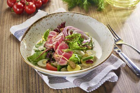 Fried tuna fish salad on wooden table