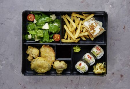 Fresh Food Portion in Japanese Bento Box with Sushi Rolls,