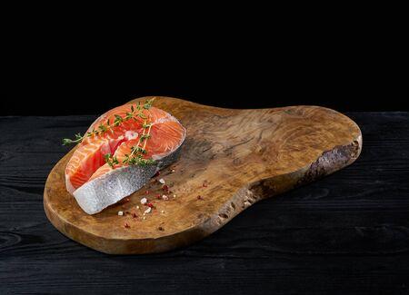 Raw salmon steak on the wooden board Imagens