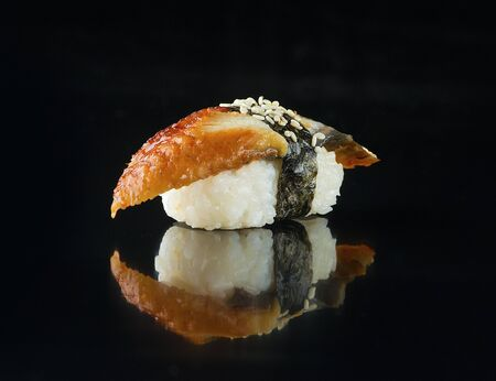 Smoked eel sushi on a black background
