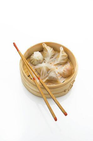 Dim sums in a bamboo steamer with chopsticks on white background Stock fotó