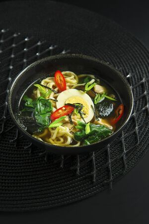 Traditional asian soup in bowl on black background Imagens