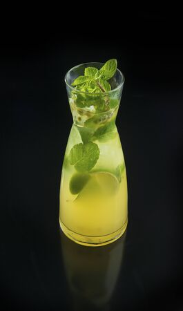 Fresh summer citrus lemonade with lime and mint in glass and jug on the black background
