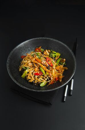 Asian noodles with chicken, vegetables in bowl, black background. Space for text.