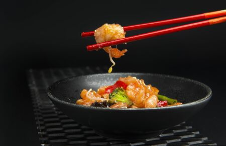 Prawn in chopstick hand, asian food concept Imagens