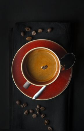 Coffee cup and coffee beans on dark background Imagens