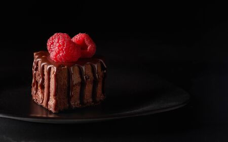Chocolate cake with raspberries on black background