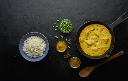 Cooking tasty butter chicken curry dish with rice in a cast iron pan Imagens