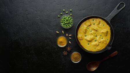 Cooking tasty chicken curry in pan on black background. Flat lay, top view with copy space