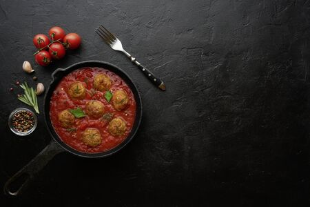 Cooking meatballs with tomato sauce in black pan. Flat lay, top view with copy space