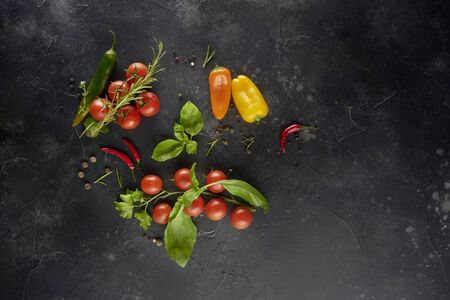Tomatoes with basil and sea salt on black slate background. Top view with copy space.