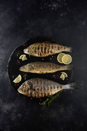Grilled fish on black background with fresh herbs, lemon and colorful pappercorn on black background, top view. Mediterranean luxurious seafood concept.