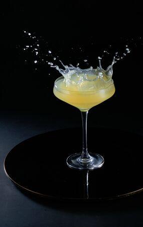 cocktail splashing into glass on black background