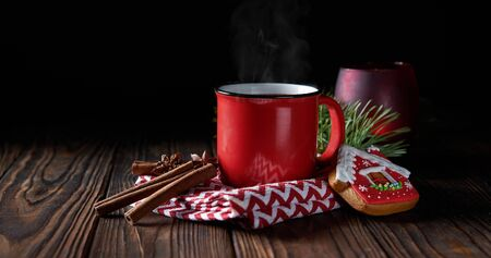 Homemade spicy hot chocolate with cinnamon in enamel mug on wooden table
