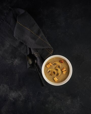 Mushroom soup in white bowl with croutons on dark background. Top view with copy space Imagens