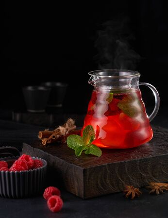 Hot red fruit tea with raspberries in a glass teapot with mint on a wooden background Imagens