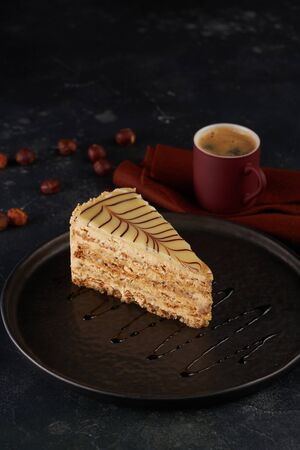 Piece of cake with nuts on black plate