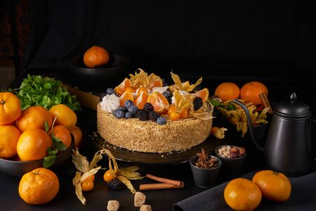 Homemade cake decorated with clementines, kumquat and fresh berries on dark background