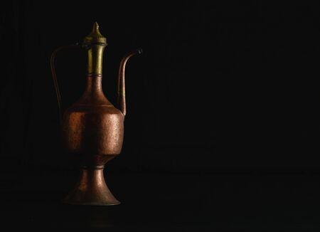Old arabic metal jar on black background