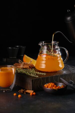 Herbal tea with sea buckthorn in a glass teapot, on wooden board.