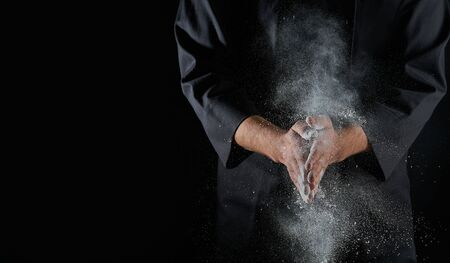 Male hands and splash of white wheat flour on a black background Imagens