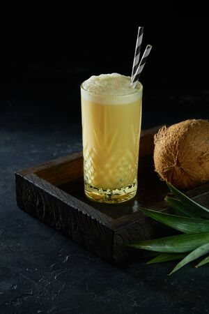 Glass of pina colada cocktail with rum, pineapple juice and decorated with coconut