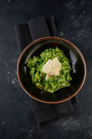 Pasta with pesto sauce on black plate. Top view