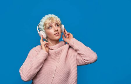 Happy woman listens to music in headphones, wearing winter knitted hat and sweater over blue background