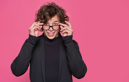 Young handsome man wearing glasses over pink background Stockfoto