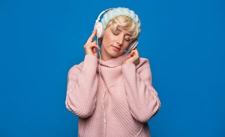 Beautiful young woman in headphones listening to music, wearing winter knitted hat and sweater on blue background
