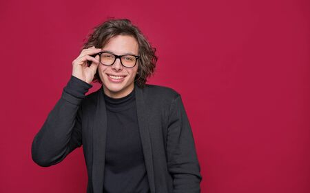Young stylish friendly man wearing eyeglasses standing isolated on red background and looking at camera