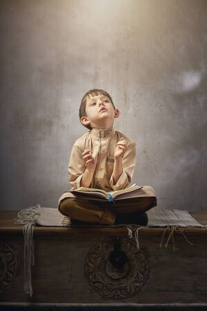 Muslim boy in prayer cap and arabic clothes with rosary beads and holy Koran book praying to Allah, ramadan kareem concept young kid spiritual peaceful moment inside eastern traditional interior