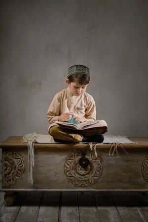 Little muslim boy in prayer cap and arabic clothes with rosary beads reading holy quran book praying to Allah, ramadan kareem concept kid spiritual peaceful moment inside eastern traditional interior Stockfoto