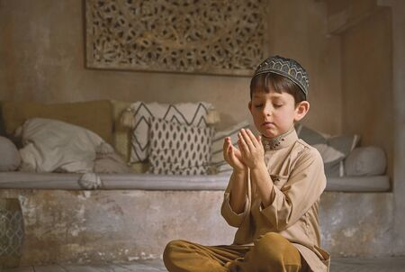 Little muslim boy in prayer cap and arabic clothes with rosary beads and holy Koran book praying to Allah, ramadan kareem concept young kid spiritual peaceful moment inside eastern traditional interior