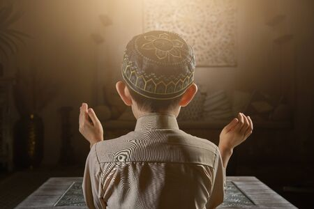 Young muslim boy in prayer cap and arabic clothes with rosary beads and holy Koran book praying to Allah, ramadan kareem concept young kid spiritual peaceful moment inside eastern traditional interior