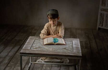 Young muslim boy in prayer cap and arabic clothes with rosary beads reading holy quran book praying to Allah, ramadan kareem concept kid spiritual peaceful moment inside eastern traditional interior Banque d'images