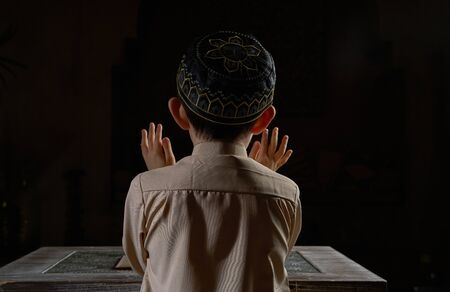 Back view of muslim boy in prayer cap and arabic clothes with holy Koran book praying to Allah, ramadan kareem concept young kid in spiritual peaceful moment inside eastern traditional interior