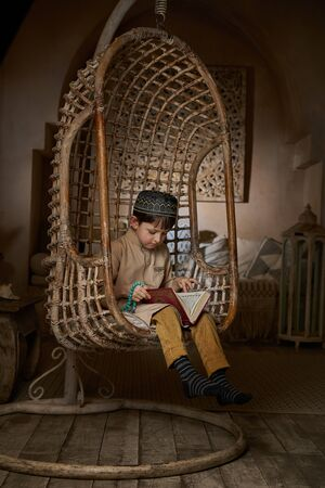 Little muslim boy in prayer cap and arabic clothes with rosary beads reading holy koran book praying to Allah, prophet Muhammad holy spirit religion symbol concept inside eastern traditional interior Stockfoto