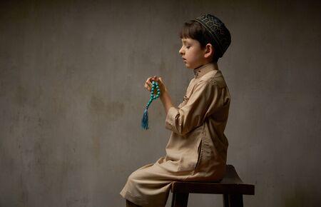 Little muslim boy in prayer cap and arabic clothes with rosary beads praying to Allah, ramadan kareem concept kid spiritual peaceful moment Stockfoto - 140525006