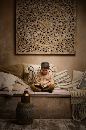 Muslim boy in prayer cap and arabic clothes with rosary beads reading holy quaran book praying to Allah, prophet Muhammad holy spirit religion symbol concept inside eastern traditional interior Stockfoto - 140525011
