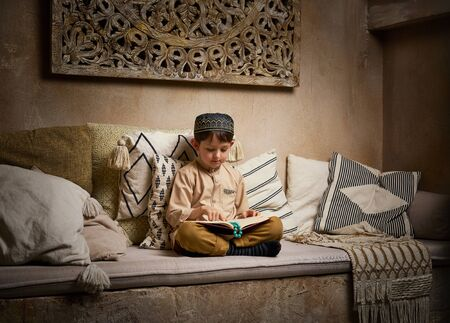 Muslim boy in prayer cap and arabic clothes with rosary beads reading holy koran book praying to Allah, prophet Muhammad holy spirit religion symbol concept inside eastern traditional interior