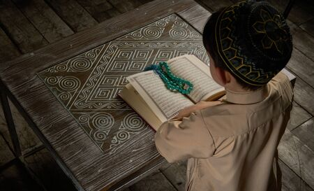 Muslim boy in arabic clothes reading holy Koran book and praying to Allah, ramadan celebration concept young kid in spiritual peaceful moment inside eastern traditional interior