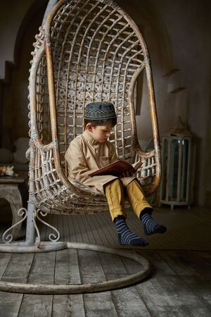 Little muslim boy in arabic clothes with rosary beads reading holy quran book praying to Allah, ramadan kareem concept kid spiritual peaceful moment inside eastern traditional interior